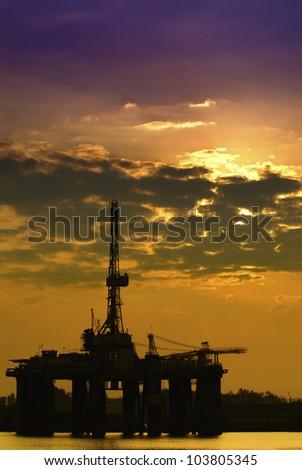 Oil rig platform in colorful sunrise. - stock photo
