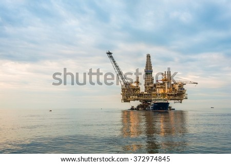 Oil rig platform in the calm sea - stock photo