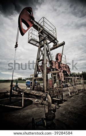 Oil rig pump dramaticly underexposed against contrast cloudy sky low angle view - stock photo