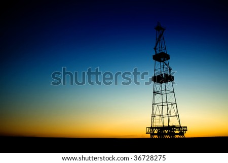 Oil rig silhouette over blue sky - stock photo