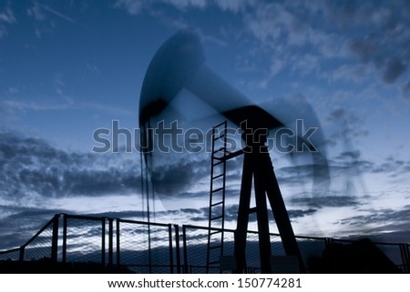 oil rig silhouette working at sunset lighting - stock photo