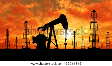 Oil rig silhouettes over orange sky