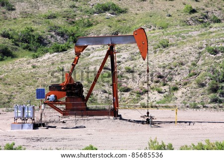 Oil rig sitting in the middle of the prairie. - stock photo