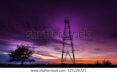 Oil rig structure and lonely tree profiled on dramatic sunset sky - stock photo