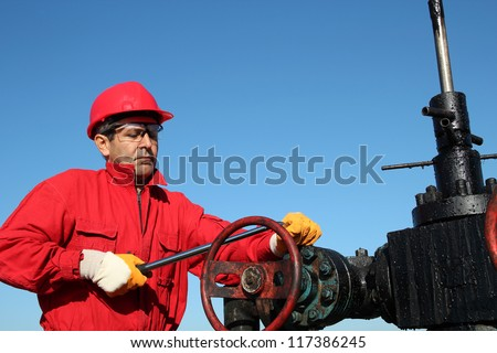 Oil Rig Valve Technician at Work. Oil and Gas Industry. Oil worker wearing red coveralls and red helmet, working at pump jack oil well.