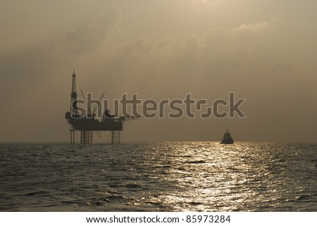 Oil rig with standby boat in the ocean - stock photo