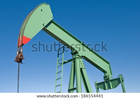 oil rig working on blue sky background - stock photo