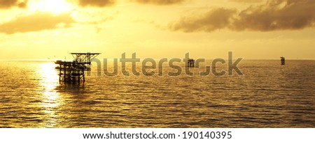Oil rigs and a golden sunrise - stock photo