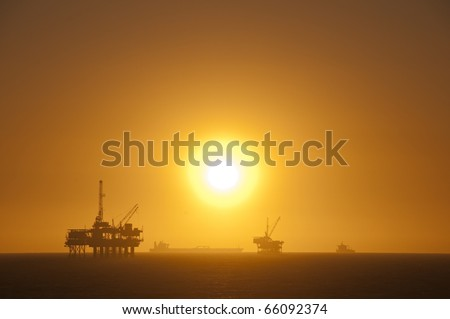 Oil rigs, ship and sunset in the ocean. Huntington Beach, California. - stock photo