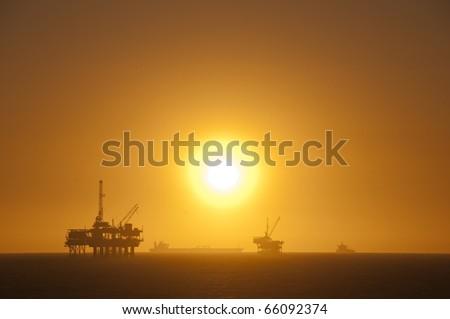Oil rigs, ship and sunset in the ocean. Huntington Beach, California. - stock photo