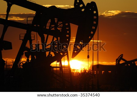 oil rigs silhouette over orange sky - stock photo