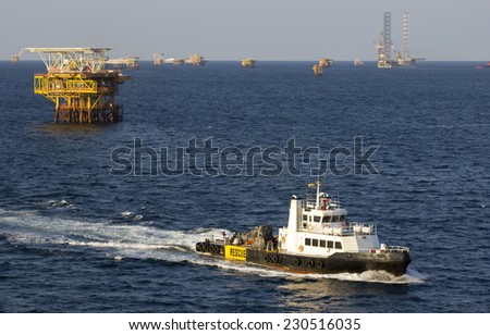 Oil rigs with standby boat for transporting people to nearby rigs - stock photo