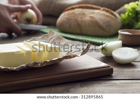 oil, salt , onion, a loaf of bread, cleaning of onions in the background