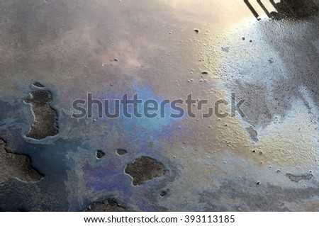 Oil spill on asphalt road background or texture - stock photo