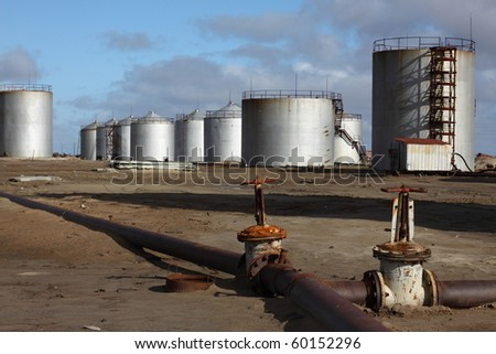 Oil tank at industrial site with ladders - stock photo