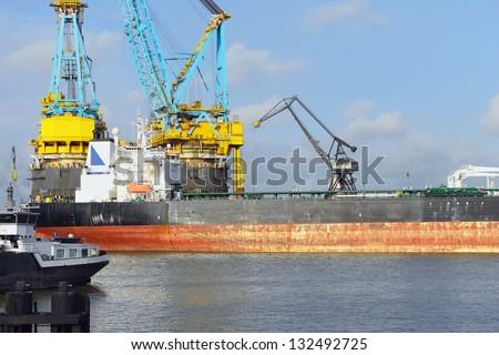 oil tanker and vessel crane in rotterdam harbor - stock photo