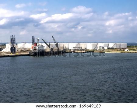 Oil Tanker Offloading to Refinery Storage Tanks - stock photo