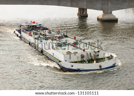 Oil tanker sailing in the river under the bridge - stock photo