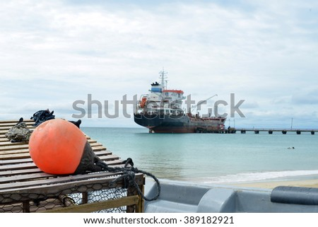 oil tanker ship at dock with lobster pot trap and buoy at Picnic Center Beach Big Corn Island Nicaragua Central America - stock photo