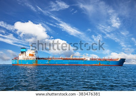 Oil tanker ship at sea on a background of blue sky. - stock photo