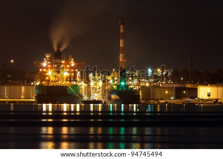 Oil tanker unloading cargo at an oil refinery illuminated at night - stock photo