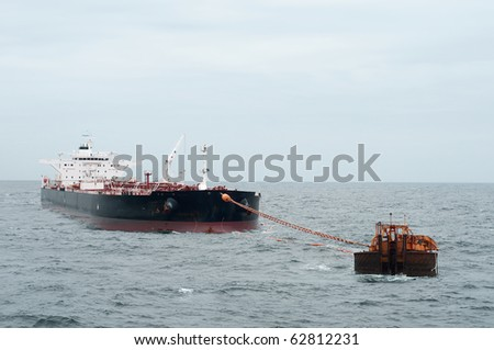 Oil tanker vessel anchored in offshore area, been loaded by some oil rig - stock photo