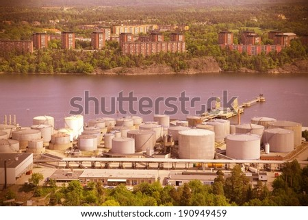 Oil tanks and other silos at Stockholm sea port. Sweden. Cross processed color tone - retro image filtered style. - stock photo