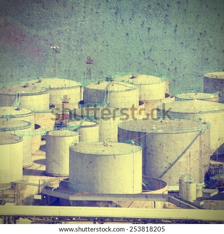 Oil tanks and other silos at Stockholm seaport, Sweden. Filtered and cross processed vintage image style. - stock photo