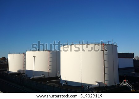 oil tanks in a row under blue sky