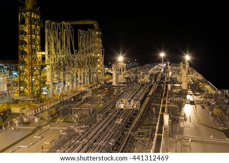 Oil terminal with moored tanker at night.