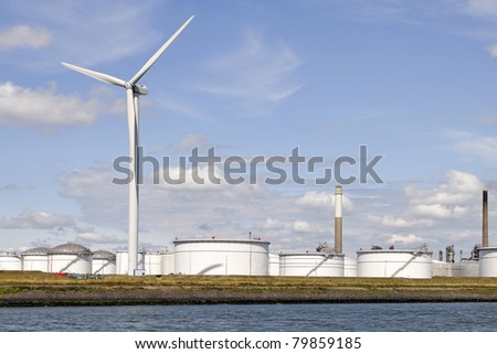 oil terminal with wind turbine for clean energy - stock photo