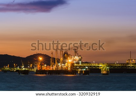 Oil transfer station on the sea with sunset