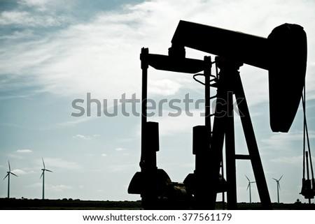 Oil well and windmills in Ayoluengo de la Lora, Burgo Province, Castilla Leon, Spain. - stock photo