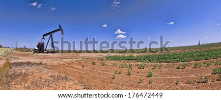 Oil well pumper with room for your type. - stock photo