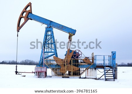Oil wells are drilling oil at winter - stock photo