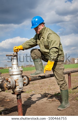 Oil worker check oil pump - stock photo