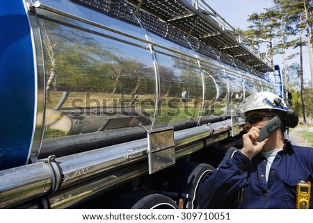 oil worker, driver outside a large fuel and oil truck inside refinery - stock photo
