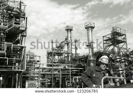 oil-worker, engineer, with pipelines machinery, large refinery in background, duplex toning concept - stock photo