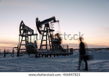 Oil worker in a oilfield. Pump jack and engineer on a winter sunset sky background. Western Siberia. Blurred motion. - stock photo