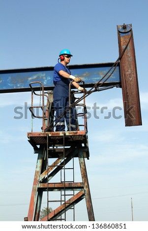 oil worker in blue uniform standing at pump jack - stock photo