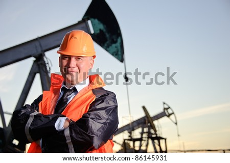 Oil worker in orange uniform and helmet on of background the pump jack and sunset sky.