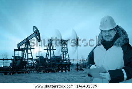 Oil worker in orange uniform and helmet on of background the pump jacks and sunset sky. Monochrome. - stock photo