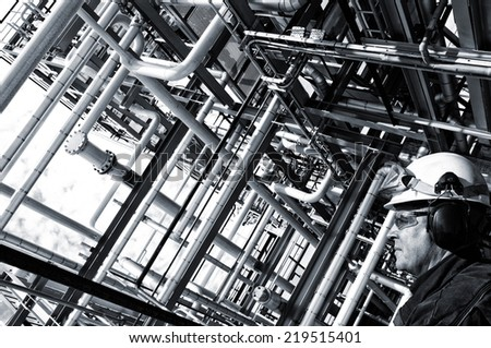 oil worker in profile with large pipelines construction, analog processing effect - stock photo
