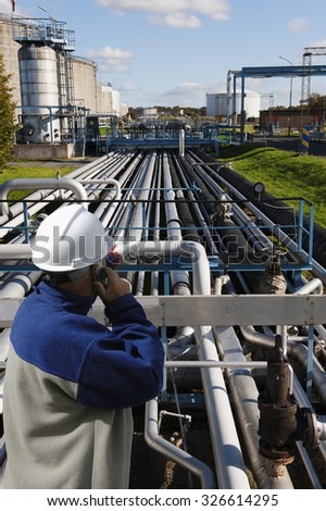oil worker pointing out over long pipelines constructions leading to fuel tanks - stock photo