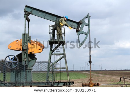 oil worker standing at pump jack - stock photo