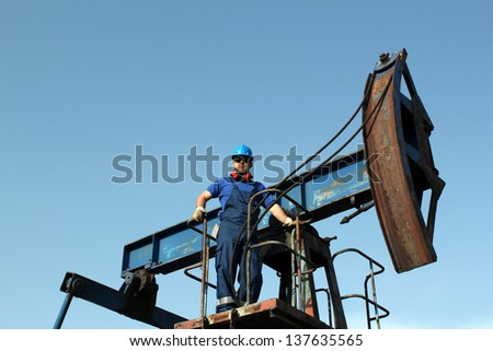 oil worker standing on pump jack - stock photo
