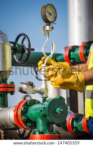 oil worker turning valve - stock photo