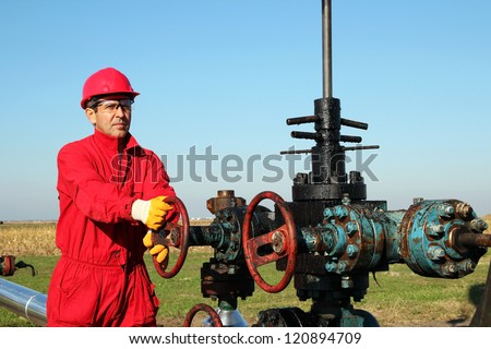 Oil worker turning valve on oil rig. - stock photo