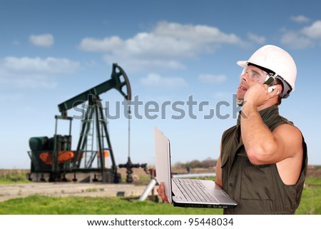 oil worker with laptop and phone - stock photo