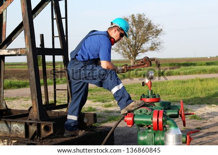 oil worker with wrench check pipeline - stock photo